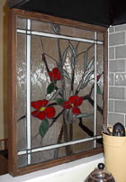 In this glass art piece, commissioned to partition off a portion of the newly-remodeled kitchen in a prairie-style bungalow in a historic urban neighborhood near the U of A, Ochoa Stained Glass Artists utilize a floral design with an oriental flare as the focal point, choosing a clear textured glass as a background that dramatically adds to the effect.