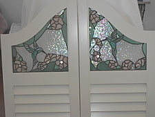 A set of sparkling café doors created for a Northwest Tucson home in cooperation with Whitney Burns Shutter Company. The stained glass portion incorporates the client's favorite flower and hummingbirds to bring a colorful bit of nature to the entryway that connects her kitchen and family room.