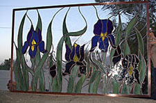 "In this transom panel created by Ochoa Stained Glass for a home in the Tucson Mountains, the artist has used a clear textured glass known as ""baroque"" to create the feeling that this field of Irises are blowing in the wind."